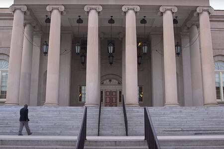 Person walks up the front steps of a large building towards the entrance.