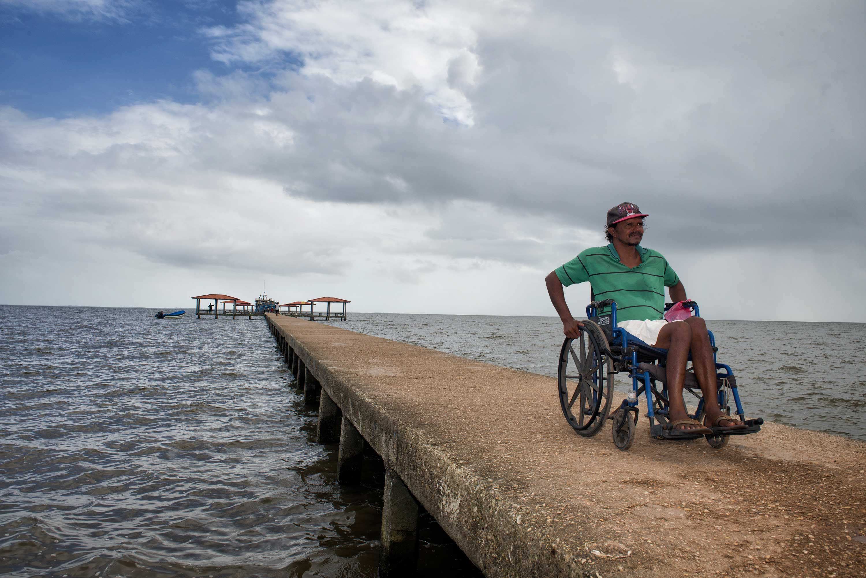 A Honduran man in a baseball cap, green polo, and white shorts pushes himself in a wheelchair down a pier against the backdrop of the ocean.