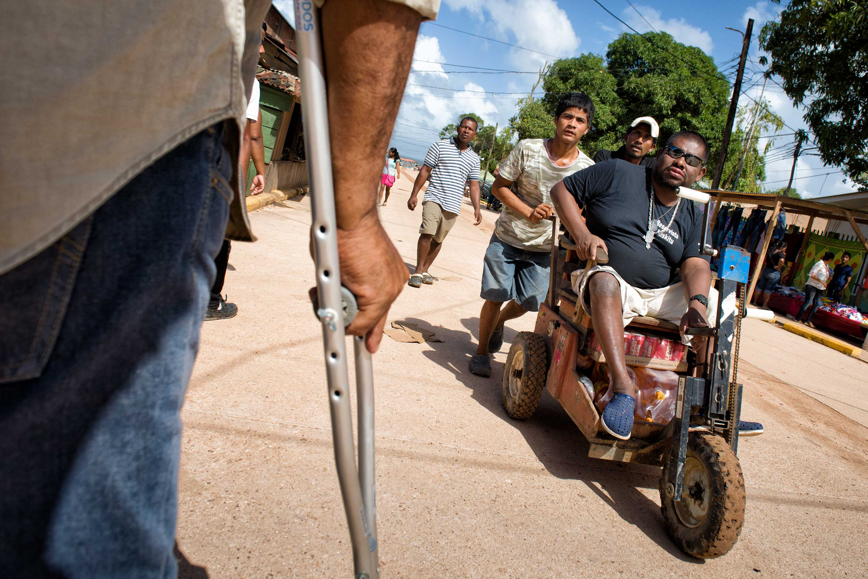 In a foreground, the back of a person person using crutches while a man in sunglasses rides a motorized chair is pushed by two men .