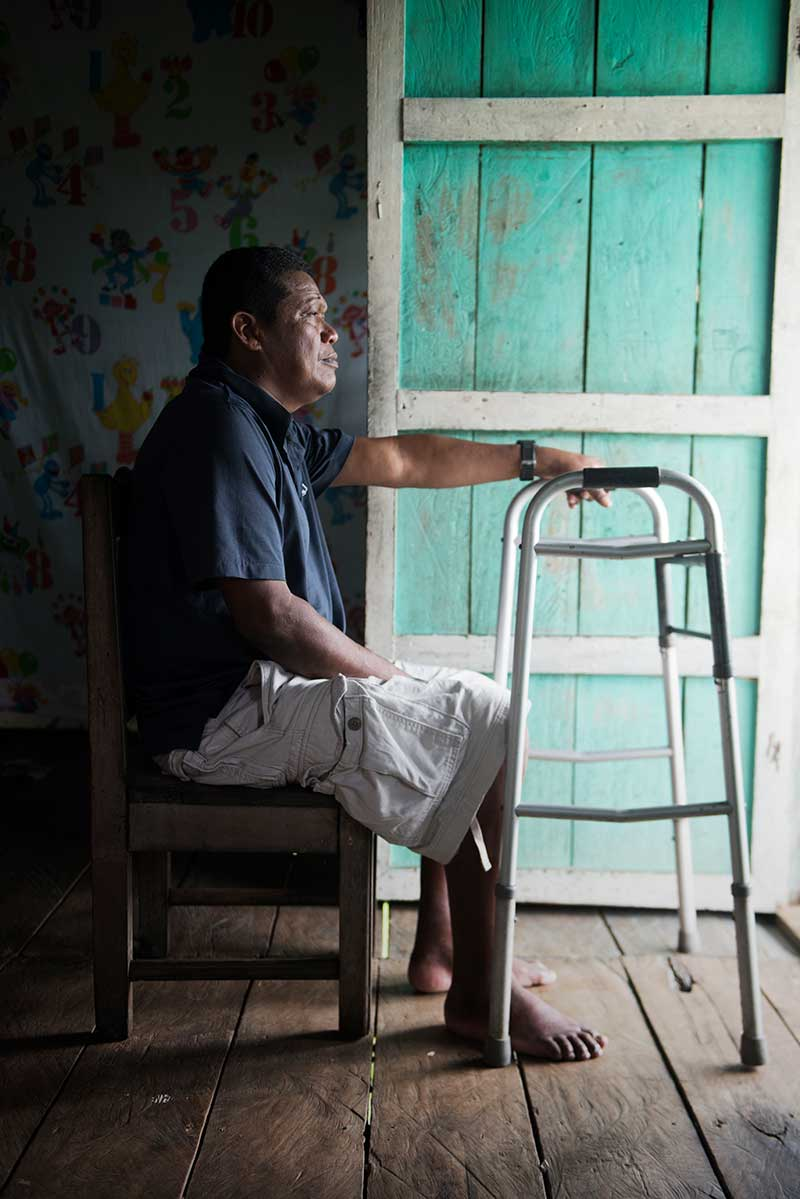 A Honduran man in a blue shirt and white cargo shorts sits on a chair, looking out his front door with his left hand resting on a walker.