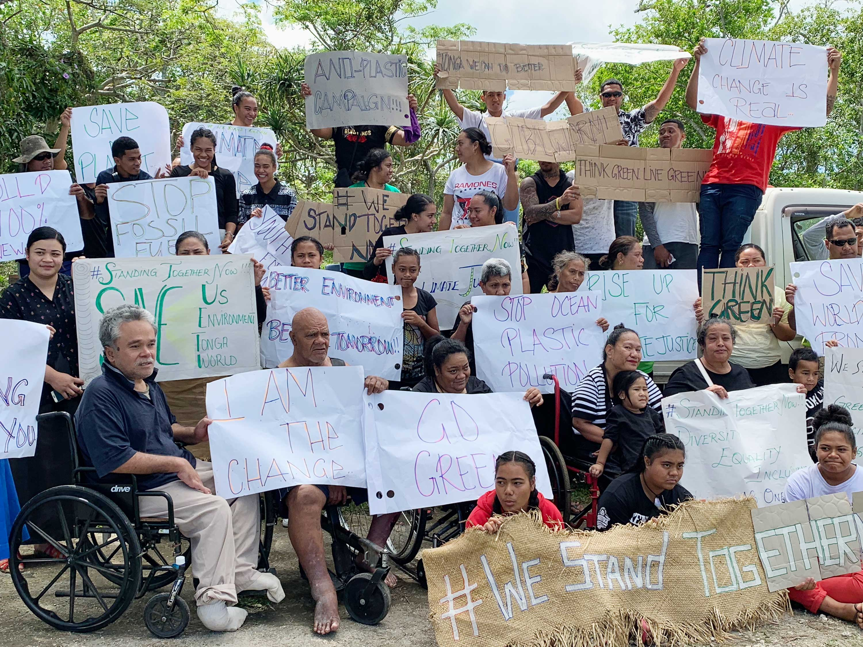 People with disabilities, some in wheelchairs, hold up signs on paper and tarp protesting against fossil fuels, plastics, and environmental destruction.