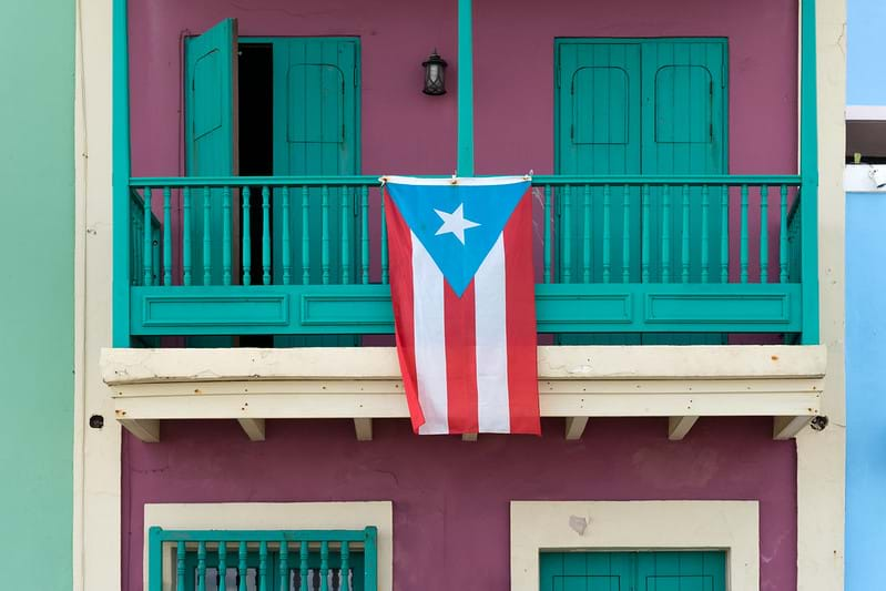 The Puerto Rican flag, with a white star inside a blue triangle backed by five red and white stripes, hangs over the balcony of a colorful old building.