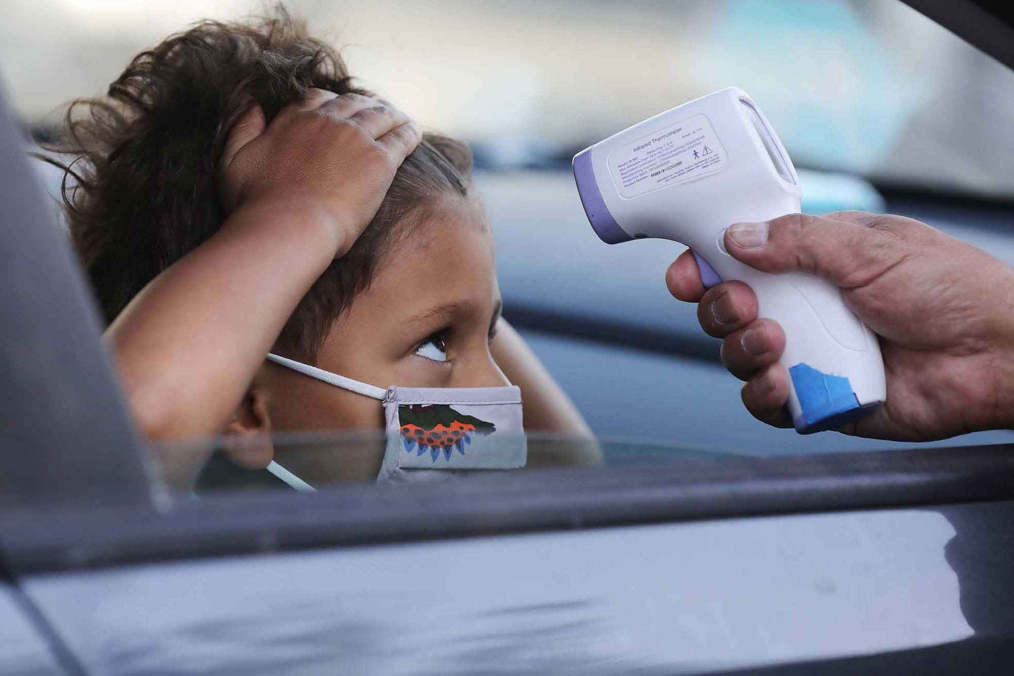 A young student inside a car wearing a medical mask pulls their hair back as a hand with a thermometer is pointed to their head.