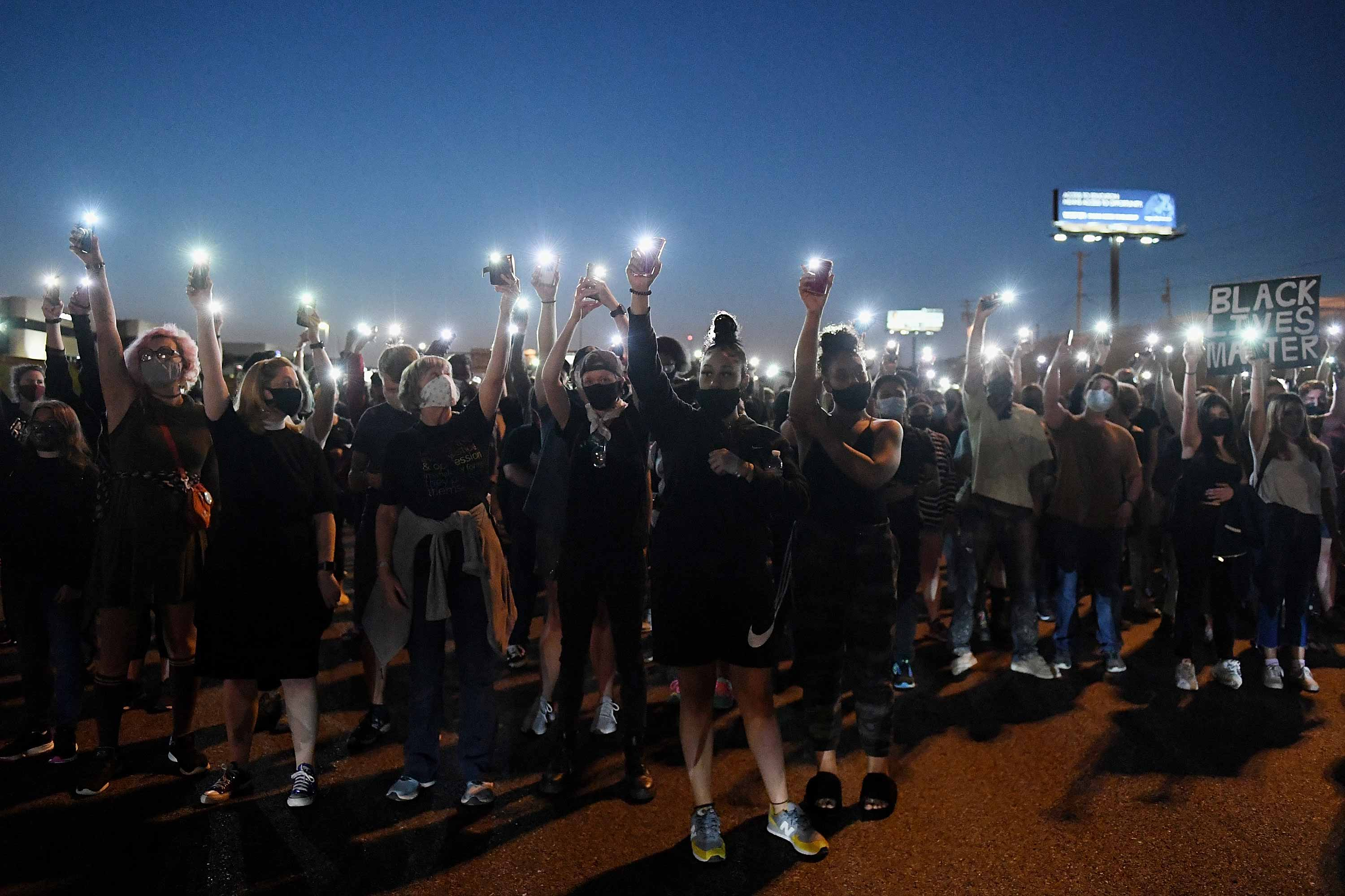 Demonstrators wearing protective masks raise their phones with their flashlights in a crowd dotted with lights.