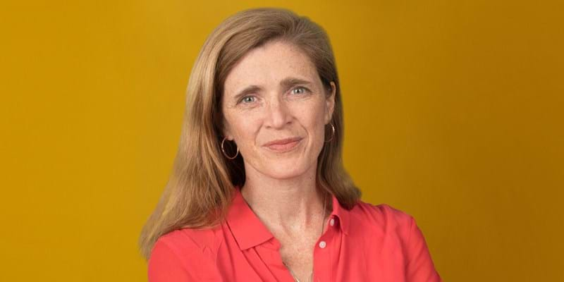 Portrait of Samantha Power in a pinkish-red blouse against a gold background. ©Martha Stewart, 2020