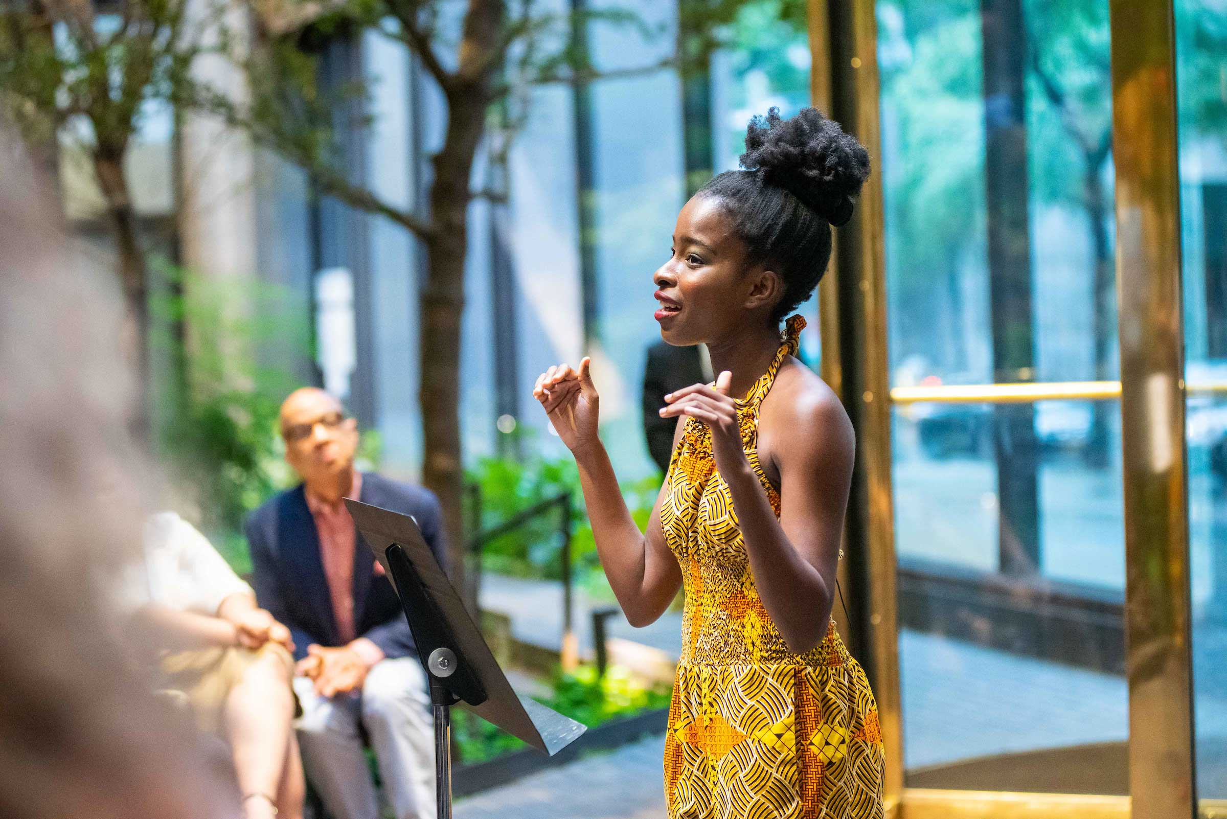 Amanda Gorman gestures with her hands as she recites a poem wearing a patterned yellow dress behind a music stand in the Ford Foundation Garden. Darren Walker looks on in the background. PHOTO: Jane Kratochvil