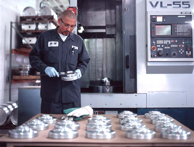 An individual inspects equipment while at a manufacturing facility.