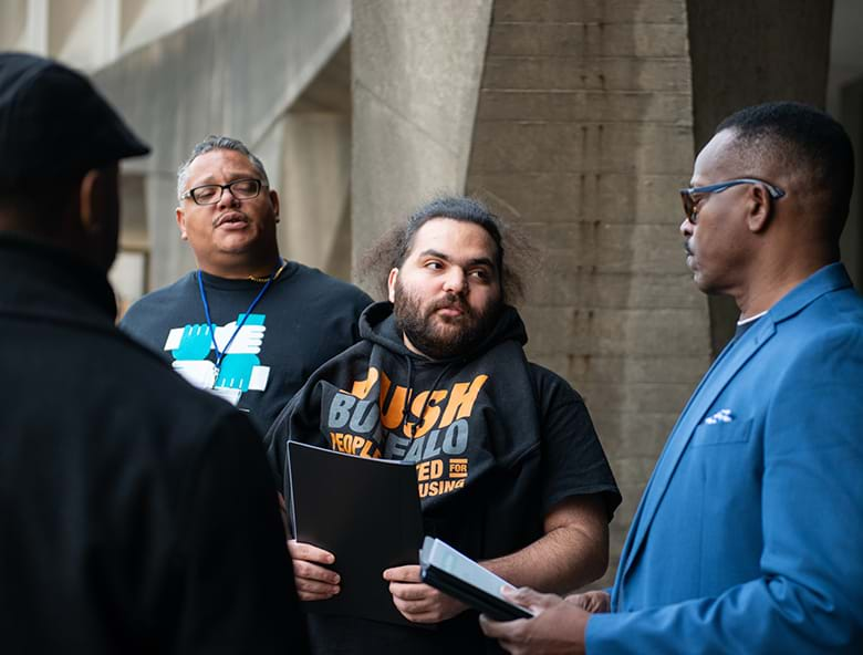 Image of a racially diverse group of four men talking near the entryway of a large building. Photo credit: Bora Chung/Survival Media Agency