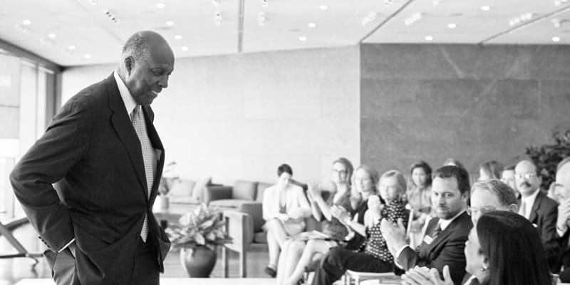 Vernon Jordan in a dark suit smiles towards a crowd with his hands in his pocket as the audience applauds him in a sunny room.