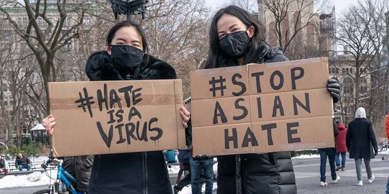 "Protestors hold signs that read ""hate is a virus"" and ""stop Asian hate"" at the End The Violence Towards Asians rally in Washington Square Park. Photo by Dia Dipasupil/Getty Images"