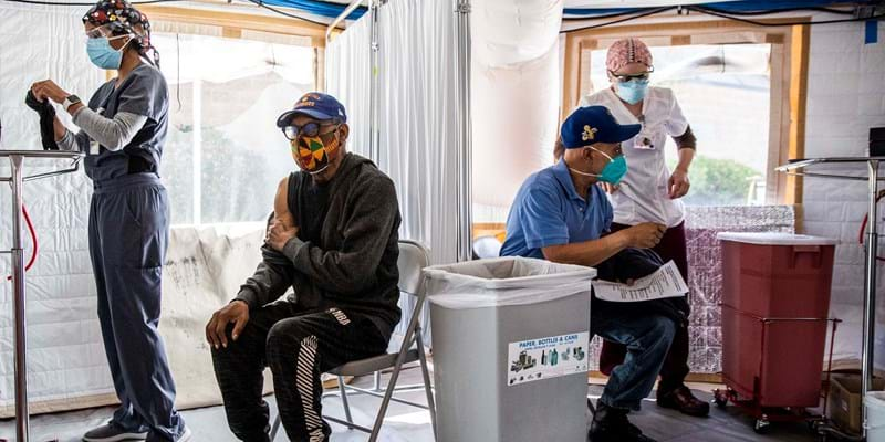 Four individuals wearing masks are in a COVID-19 vaccination center. Two of the individuals are student nurses, while the other two are there to receive their COVID-19 vaccinations.